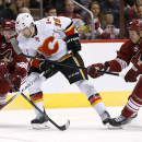 Calgary Flames' David Jones (19) tries to control the puck as Arizona Coyotes' Philip Samuelsson (25) and David Moss (18) arrive to defend during the second period of an NHL hockey game Thursday, Jan. 15, 2015, in Glendale, Ariz The Associated Press