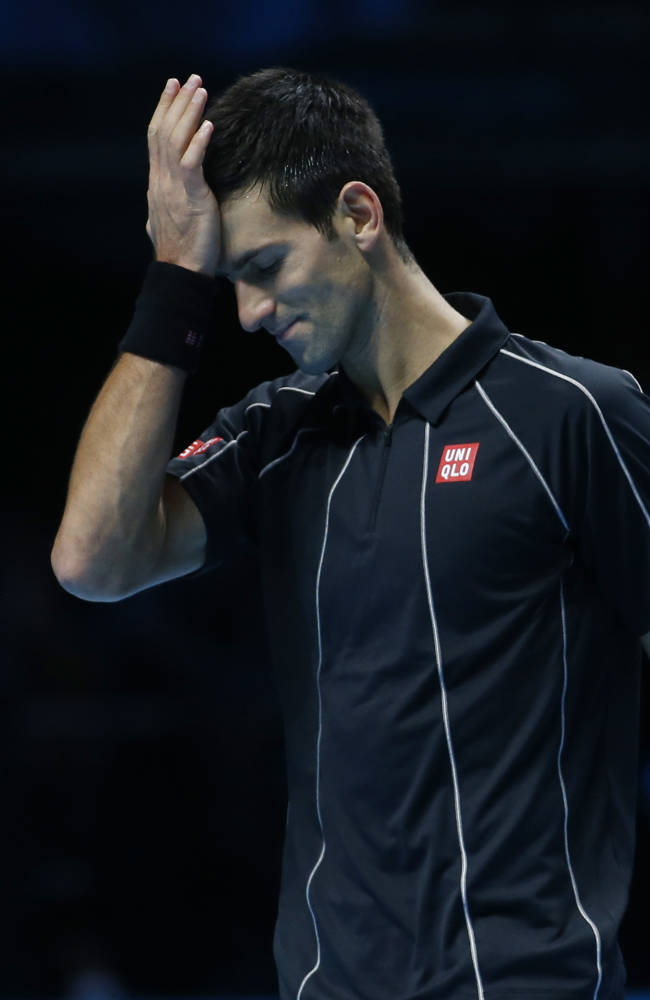Novak Djokovic of Serbia hits his head with his palm after a point lost to Stanislas Wawrinka of Switzerland during their ATP World Tour Finals single semifinal tennis match at the O2 Arena in London Sunday, Nov. 10, 2013