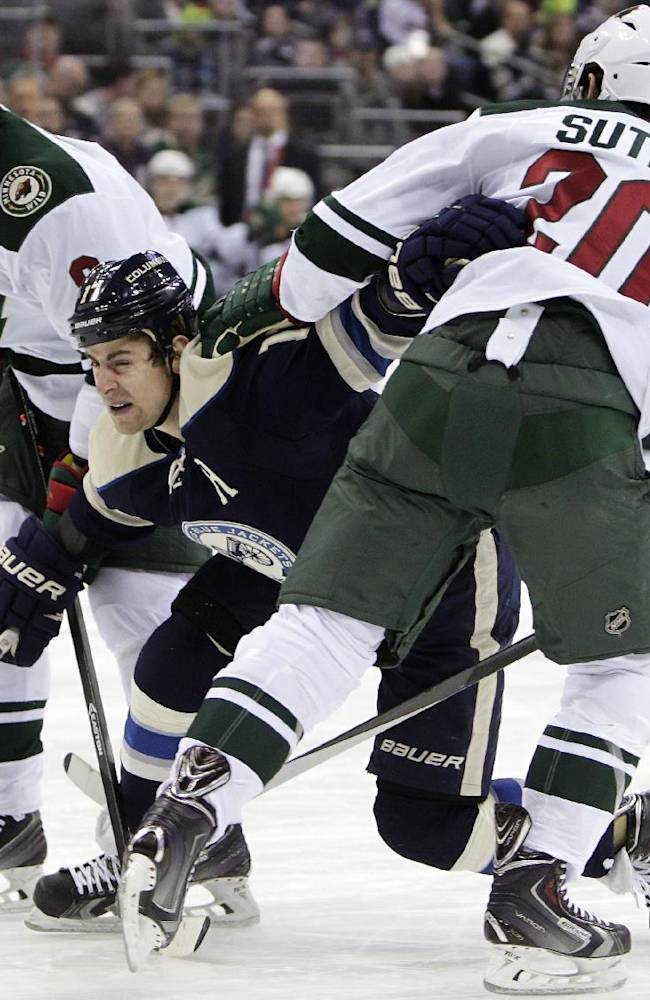 Columbus Blue Jackets' Brandon Dubinsky, center, tries to carry the puck between Minnesota Wild's Mikko Koivu, left, of Finland, and Ryan Suter during the second period of an NHL hockey game on Friday, Dec. 6, 2013, in Columbus, Ohio