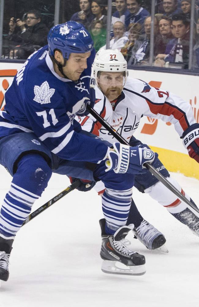 Toronto Maple Leafs right winger David Clarkson, left, battles for the puck with Washington Capitals defenseman Karl Alzner during second period NHL hockey action in Toronto, on Saturday, Nov. 23 , 2013