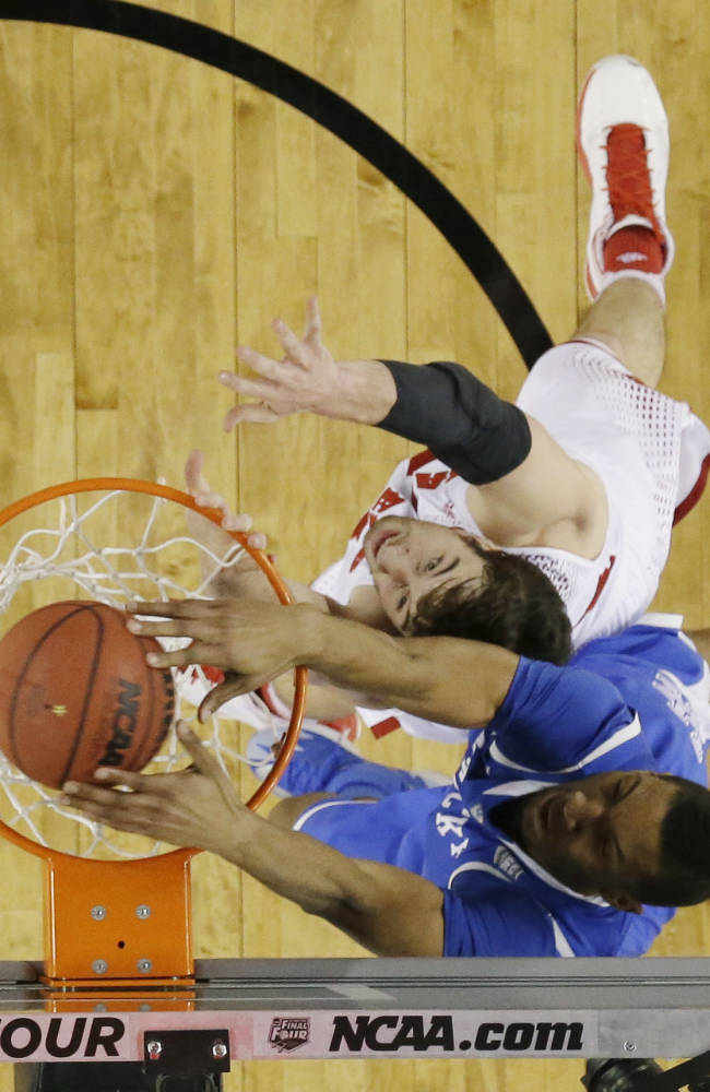 Kentucky forward Marcus Lee dunks over Wisconsin forward Frank Kaminsky during the first half of the NCAA Final Four tournament college basketball semifinal game Saturday, April 5, 2014, in Arlington, Texas