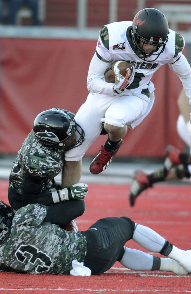 Portland State's Aaron Sibley and David Edgerson (3) snag Eastern Washinton's Cory Mitchell by the ankle during the first half of their college football game on Saturday, Nov. 23, 2013, in Cheney, Wash