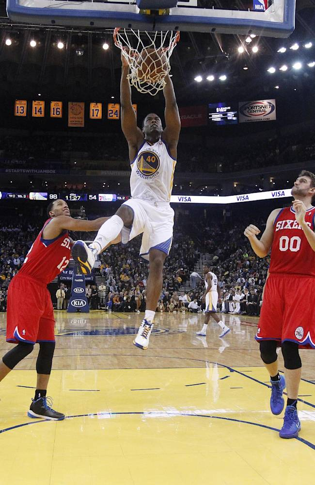 Golden State Warriors' Harrison Barnes (40) dunks over Philadelphia 76ers' Evan Turner (12) and Spencer Hawes (00) during the second half of an NBA basketball game on Monday, Feb. 10, 2014, in Oakland, Calif. Golden State won 123-80