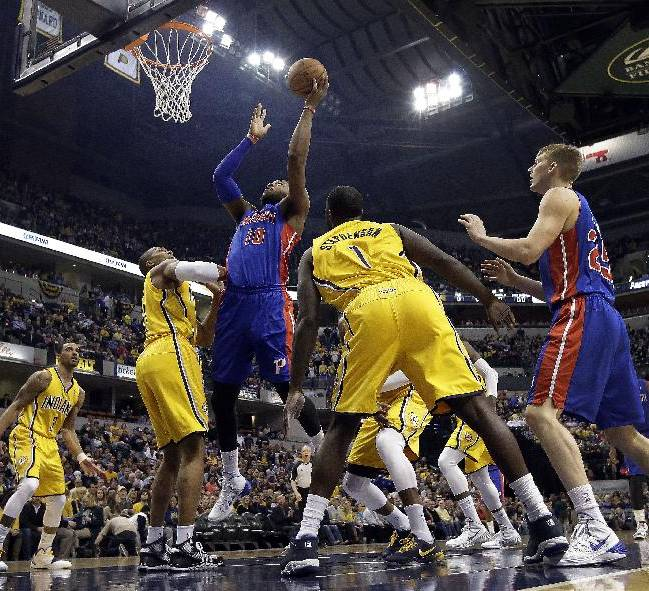 Detroit Pistons forward Greg Monroe, center, shoots between Indiana Pacers defenders David West, left, and Lance Stephenson during the first half of an NBA basketball game in Indianapolis, Wednesday, April 2, 2014