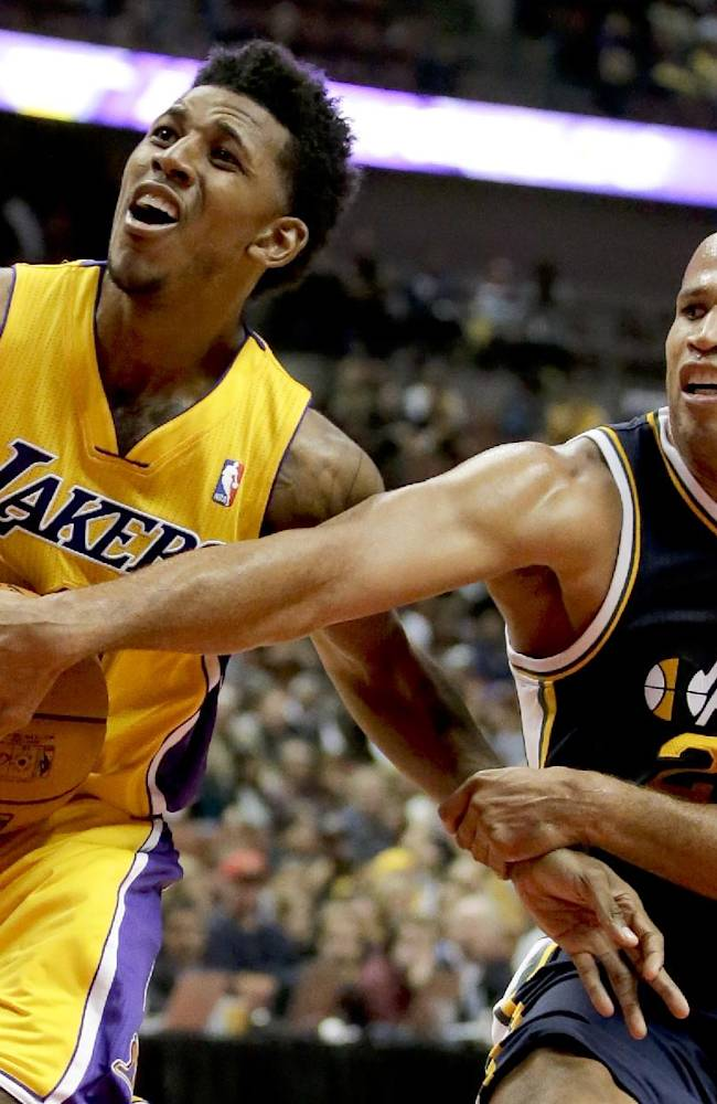Los Angeles Lakers guard Nick Young, left, gets fouled by Utah Jazz forward Richard Jefferson during the first half of a preseason NBA basketball game in Anaheim, Calif., Friday, Oct. 25, 2013