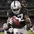 Oakland Raiders wide receiver Denarius Moore catches an 11-yard touchdown pass from quarterback Derek Carr in front of Seattle Seahawks defensive back Akeem Auguste (36) during the second quarter of an NFL preseason football game in Oakland, Calif., Thurs