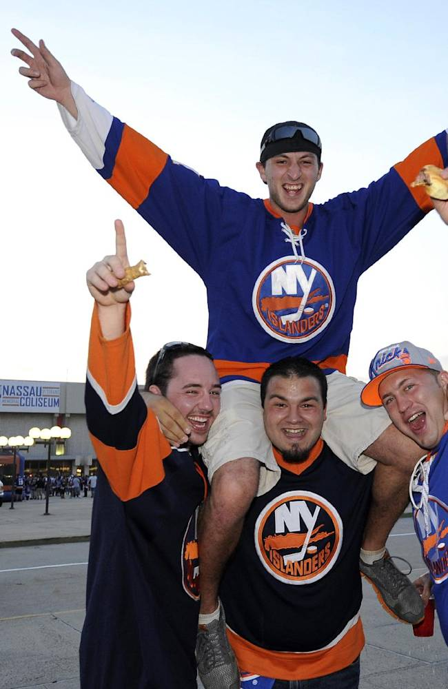 New York Islanders fans from Bellmore, N.Y., Mike Bobostahurski, top, Sean Bell, left, Anthony Dinuzzo, center, and Greg Famigiletti get fired up outside the Nassau Coliseum before an NHL hockey game against the Columbus Blue Jackets on Saturday, Oct. 5, 2013, in Uniondale, N.Y