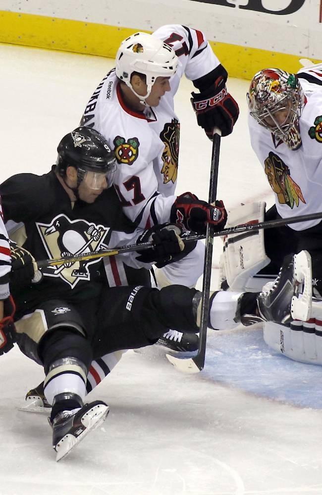 Pittsburgh Penguins' Pascal Dupuis, center is upended by Chicago Blackhawks' Sheldon Brookbank (17) after shooting the puck towards goalie Nikolai Khabibulin (39), of Russia, in the first period of an NHL preseason hockey game on Monday, Sept. 23, 2013, in Pittsburgh