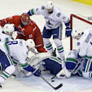 Carolina Hurricanes' Eric Staal (12) tries to score against Vancouver Canucks goalie Eddie Lack (31), of Sweden, as Canucks' Dan Hamhuis (2), Chris Tanev (8), Alex Burrows (14) and Brad Richardson (15) defend during the third period of an NHL hockey game