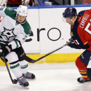 Dallas Stars left wing Antoine Roussel (21) passes the puck as Florida Panthers defenseman Brian Campbell (51) moves in during the third period of an NHL hockey game in Sunrise, Fla., Sunday, April 6, 2014 The Associated Press