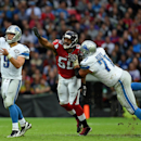 Detroit Lions quarterback Matthew Stafford (9), left, gets away a pass as teammate outside linebacker Kroy Biermann (71) blocks Atlanta Falcons defensive end Osi Umenyiora (50) during the NFL football game at Wembley Stadium, London, Sunday, Oct. 26, 2014