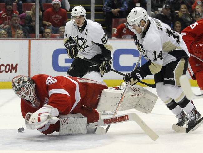 Pittsburgh Penguins' Chris Kunitz (14) gets a shot off that is redirected by Detroit Red Wings goalie Jonas Gustavsson (50), of Sweden, during the first period of an NHL hockey game on Saturday, Dec. 14, 2013, in Detroit