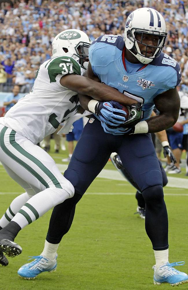 Tennessee Titans tight end Delanie Walker (82) hangs onto the ball as New York Jets free safety Jaiquawn Jarrett (37) tries to knock it loose as Walkers scores a touchdown on a 1-yard pass in the first quarter of an NFL football game on Sunday, Sept. 29, 2013, in Nashville, Tenn