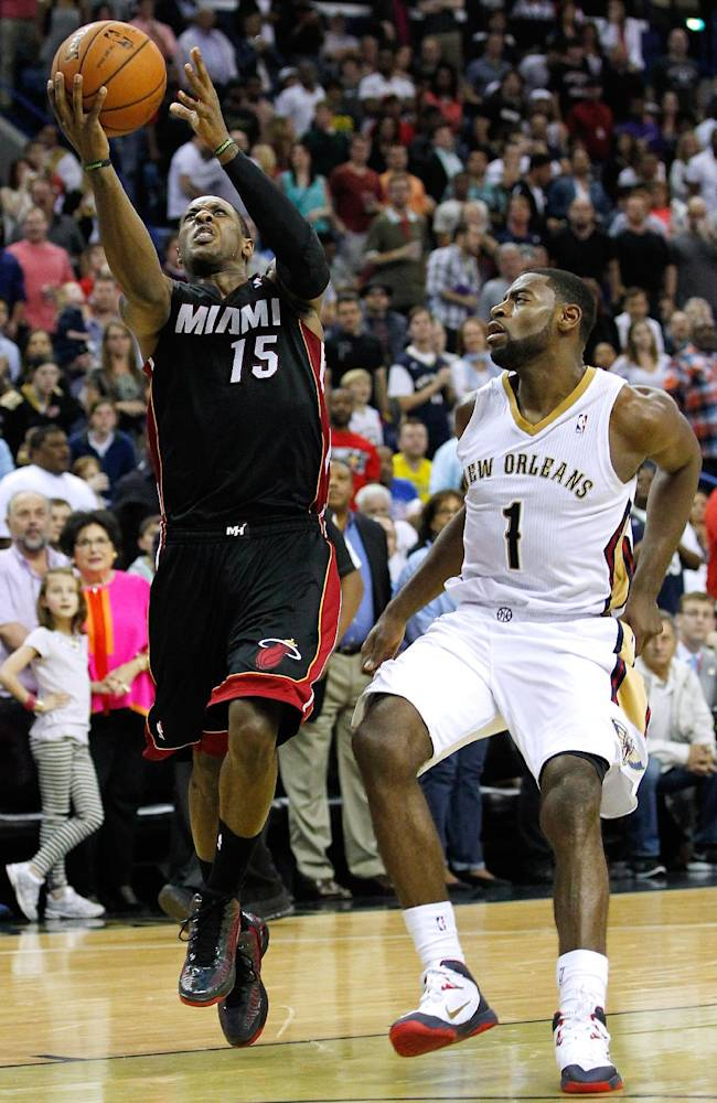 Miami Heat guard Mario Chalmers (15) drives to the basket against New Orleans Pelicans forward Tyreke Evans (1) during the second half of an NBA basketball game in New Orleans, Saturday, March 22, 2014. The Pelicans won 105-95