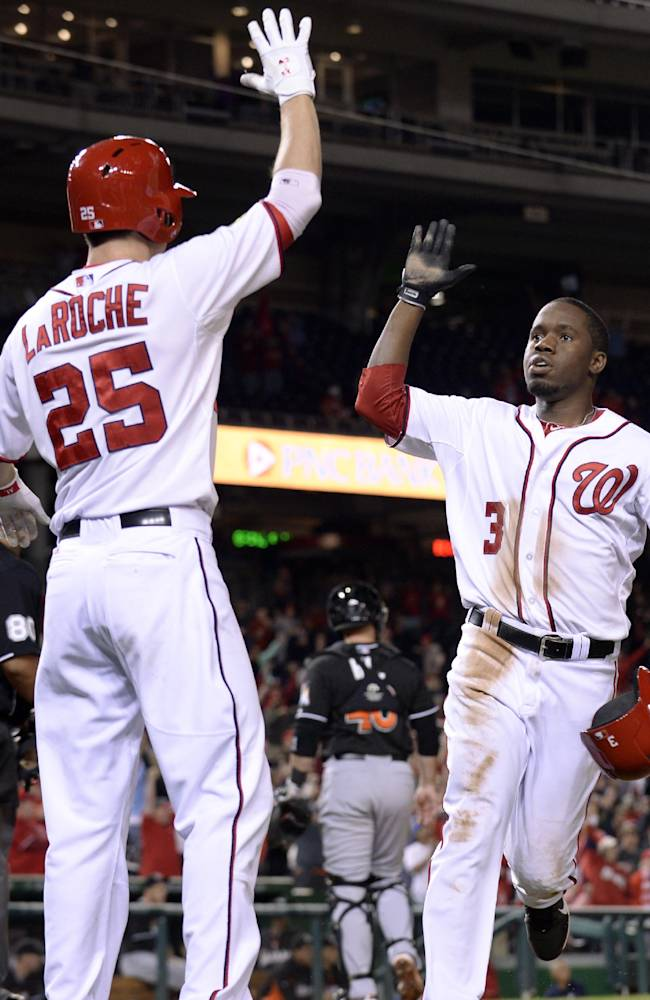 Washington Nationals' Eury Perez (3) is congratulated by teammate Adam LaRoche (25) after Perez scored the winning run to end the ninth inning of their baseball game against the Miami Marlins at Nationals Park in Washington, Sunday, Sept. 22, 2013. The Nationals won 5-4