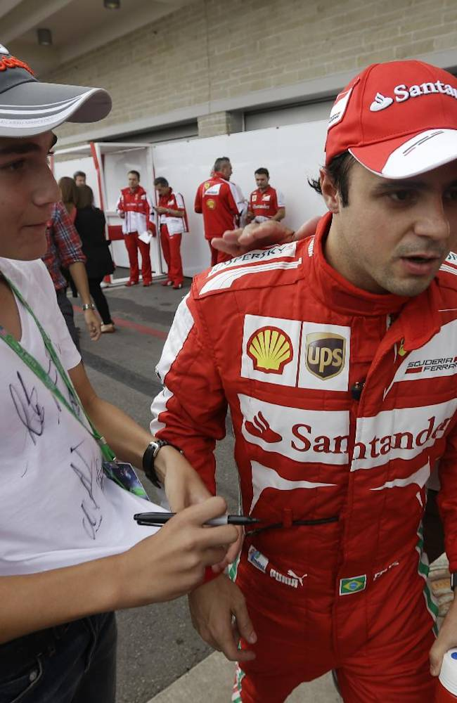 Ferrari driver Felipe Massa of Brazil walks past autographs seekers following the third practice session for the Formula One U.S. Grand Prix auto race at the Circuit of the Americas, Saturday, Nov. 16, 2013, in Austin, Texas