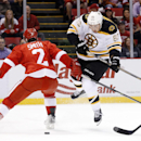 Boston Bruins left wing Brad Marchand (63) jumps to get around Detroit Red Wings defenseman Brendan Smith (2) in the first period of an NHL hockey game in Detroit, Wednesday, Oct. 15, 2014 The Associated Press