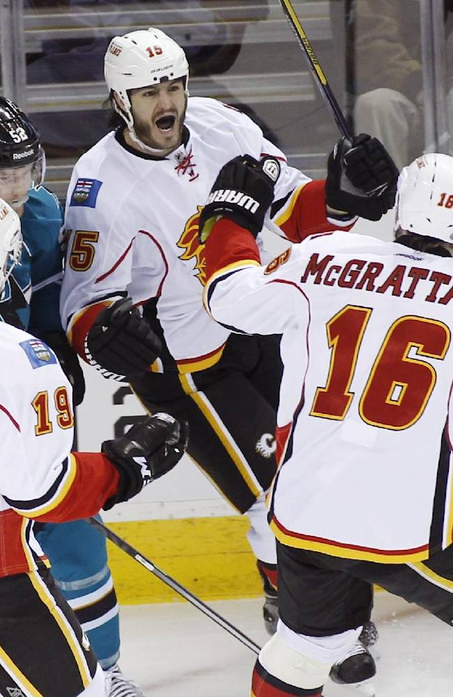 Calgary Flames' Kevin Westgarth, back, reacts after teammate Brian McGrattan (16) scored a goal against the San Jose Sharks during the first period of an NHL hockey game, Monday, Jan. 20, 2014 in San Jose, Calif.  Sharks' Matt Irwin, is at left. The Sharks beat the Flames 3-2