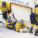 Nashville Predators goalie Pekka Rinne (35), of Finland, sprawls on the ice to block the net along with Anton Volchenkov (20), of Russia, and Colin Wilson (33) in the second period of an NHL hockey game against the Vancouver Canucks Tuesday, Jan. 13, 2015