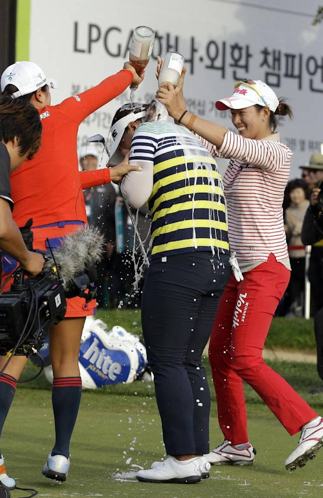 Amy Yang of South Korea, center, is sprayed with champagne by Chella Choi of South Korea, right, after winning the KEB Hana Bank Championship golf tournament at Sky72 Golf Club in Incheon, west of Seoul, South Korea, Sunday, Oct. 20, 2013