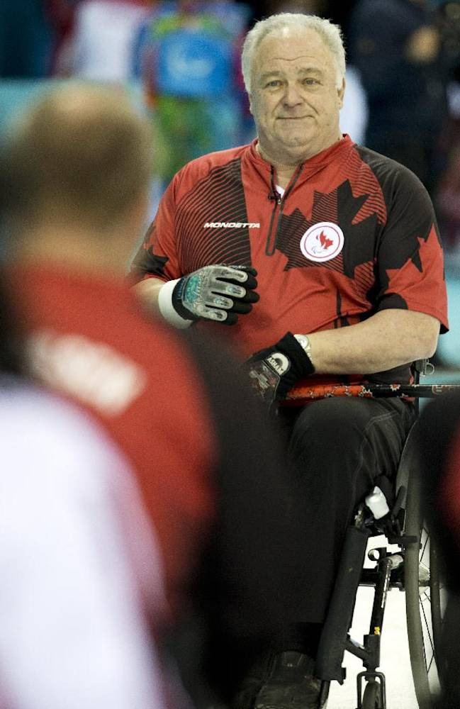 Canada's skip Jim Armstrong, center, smiles during the wheelchair curling match between Canada and Norway at the 2014 Winter Paralympics in Sochi, Russia, Monday, March 10, 2014. Norway won 8-6