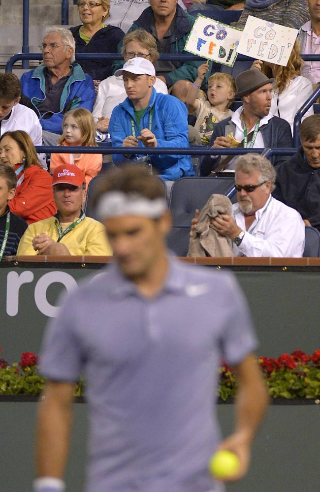 Roger Federer, of Switzerland, gets set to serve to Kevin Anderson, of South Africa, as fans hold up signs for him during the quarterfinals of the BNP Paribas Open tennis tournament, Thursday, March 13, 2014, in Indian Wells, Calif