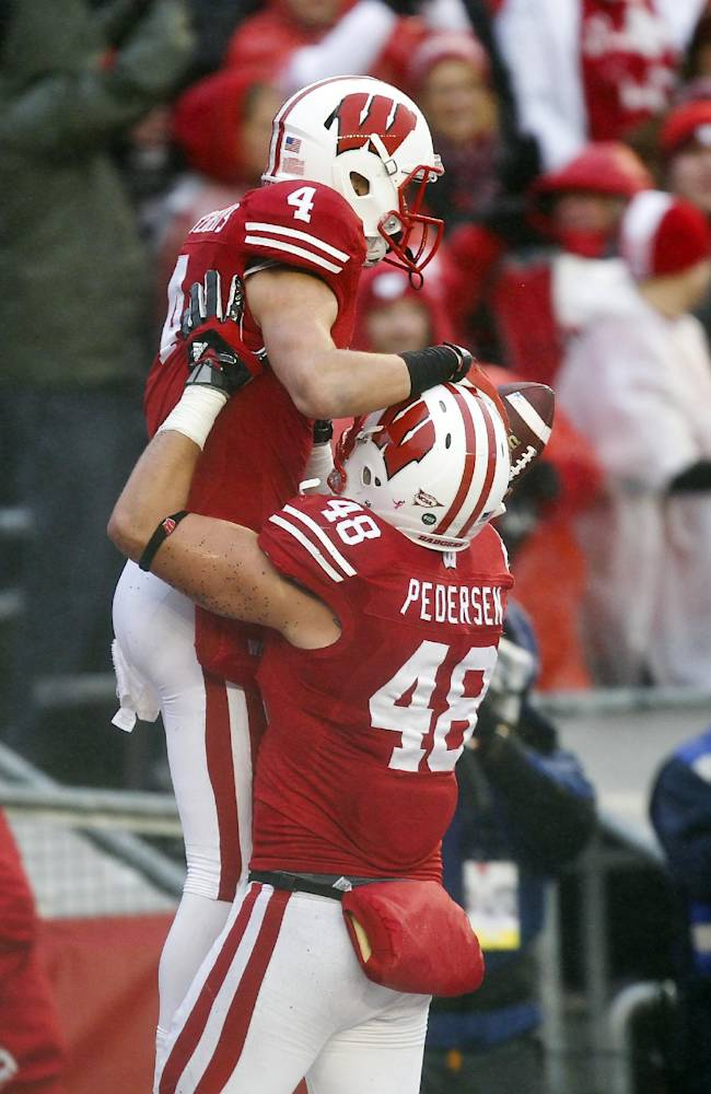 Wisconsin's Jacob Pedersen (48) lifts Jared Abbrederis after Abbrederis' touchdown during the first half of an NCAA college football game against Indiana Saturday, Nov. 16, 2013, in Madison, Wis