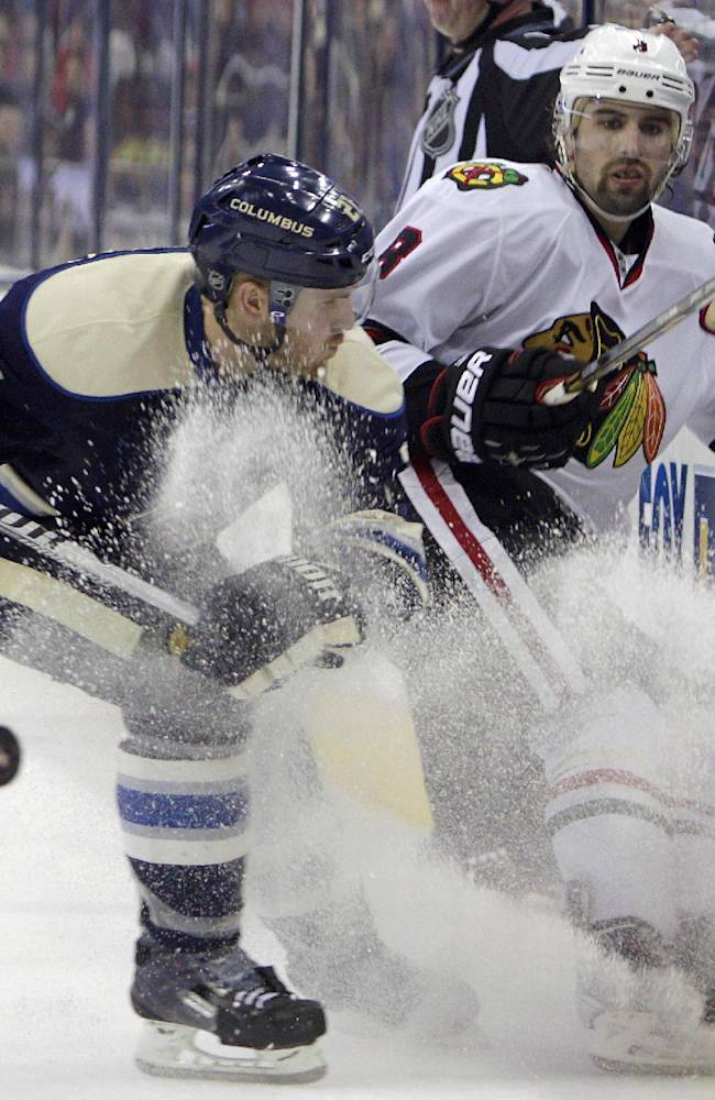 Chicago Blackhawks' Nick Leddy, right, clears the puck past Columbus Blue Jackets' James Wisniewski during the third period of an NHL hockey game on Friday, April 4, 2014, in Columbus, Ohio. The Blackhawks defeated the Blue Jackets 4-3