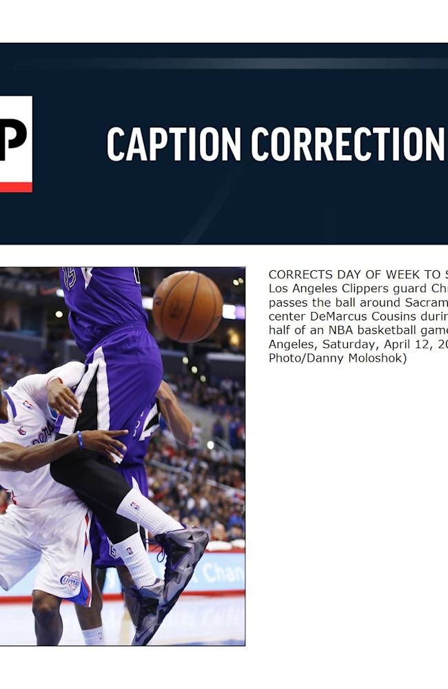 CORRECTS DAY OF WEEK TO SATURDAY - Los Angeles Clippers guard Chris Paul passes the ball around Sacramento Kings center DeMarcus Cousins during the first half of an NBA basketball game in Los Angeles, Saturday, April 12, 2014