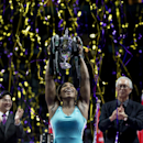 Serena Williams of the U.S. holds her trophy aloft after defeating Romania's Simona Halep in the singles final at the WTA tennis finals in Singapore, Sunday, Oct. 26, 2014. (AP Photo/Mark Baker)