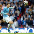 Sunderland's Jack Colback, left, vies for the ball with Manchester City's Edin Dzeko, during their English League Cup final soccer match at Wembley Stadium, London, England, Sunday, March 2, 2014