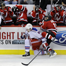Players on the New Jersey Devils bench protect themselves as New York Rangers' Chris Mueller (86) and Devils' Stephen Gionta (11) collide during the third period of an NHL hockey game Saturday, Oct. 4, 2014, in Newark, N.J. The Devils won 3-0 The Associat