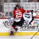 Chicago Blackhawks left wing Bryan Bickell (29) flips Winnipeg Jets left wing Adam Lowry against the boards during the first period of an NHL hockey game Friday, Jan. 16, 2015, in Chicago The Associated Press