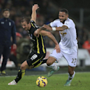 Tottenham Hotspur's Harry Kane and Swansea City's Kyle Bartley, right, chase the ball during their English Premier League soccer match at the Liberty Stadium, Swansea, Sunday Dec. 14, 2014. (AP Photo / Nick Potts, PA)