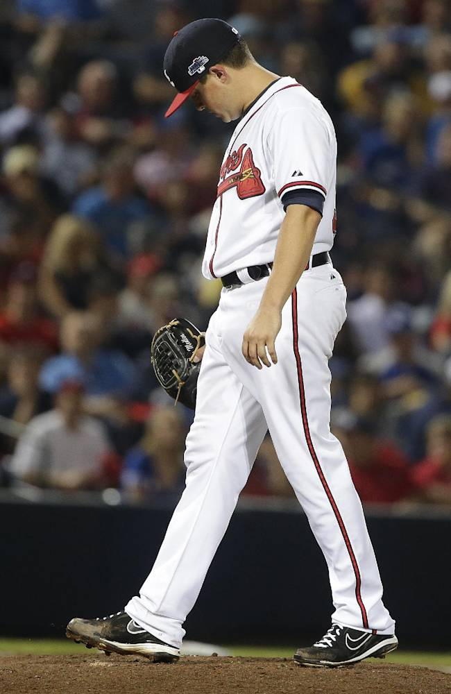 Atlanta Braves starting pitcher Kris Medlen walks to Atlanta Braves manager Fredi Gonzalez as he is relieved in the fifth inning of Game 1 of the National League Division Series against the Los Angeles Dodgers, Thursday, Oct. 3, 2013, in Atlanta