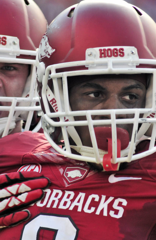 In this photo taken Aug. 31, 2013, Arkansas running back Alex Collins, right, and linebacker Austin Jones celebrate after a play during the second half of an NCAA college football game in Fayetteville, Ark. Collins was named SEC Freshman of the Year on Monday, Dec. 9, 2013