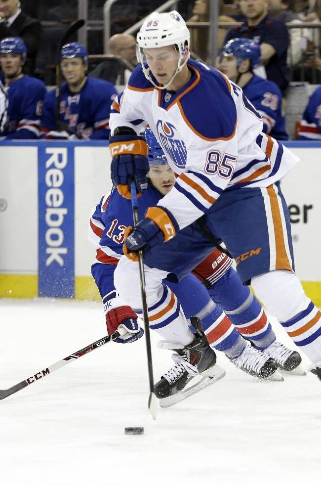 Edmonton Oilers' Martin Marincin (85), of Slovakia, gets control of the puck as New York Rangers' Daniel Carcillo (13) chases him during the second period of an NHL hockey game on Thursday, Feb. 6, 2014, in New York