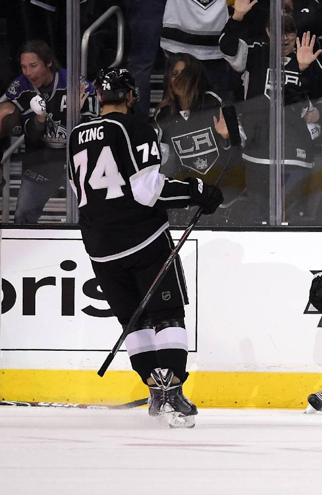 Los Angeles Kings center Anze Kopitar, right, of Slovenia, celebrates his goal with left wing Dwight King, center, as San Jose Sharks right wing Brent Burns watches during the third period in Game 6 of an NHL hockey first-round playoff series, Monday, April 28, 2014, in Los Angeles. The Kings won 4-1. (AP Photo)