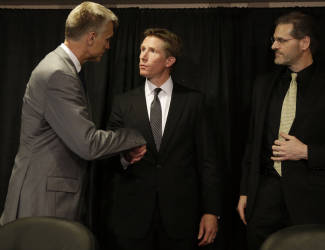 Philadelphia Flyers newly-hired head coach Dave Hakstol, center, shakes hands with team president Paul Holmgren, left, as team general manager Ron Hextall looks on after a news conference, Monday, May 18, 2015, in Philadelphia. (AP Photo/Matt Slocum)