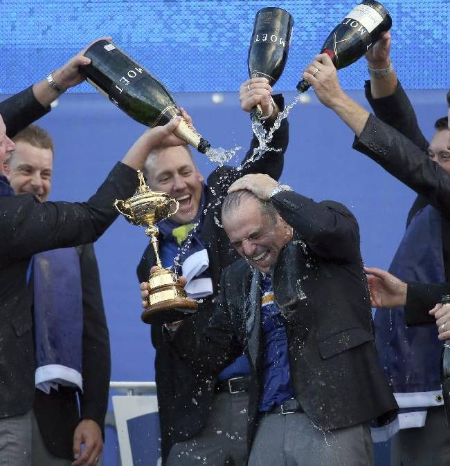 In this Sunday, Sept. 28, 2014 file photo, from left, Europe's players Jamie Donaldson, Henrik Stenson, Ian Poulter, Lee Westwood and Justin Rose pour champagne over captain Paul McGinley as they celebrate winning the 2014 Ryder Cup golf tournament, at Gleneagles, Scotland. Europe didn't need to come from behind as it did in Medinah, Illinois, USA, two years ago to win its third Ryder Cup in a row. Soon after US golfer Phil Mickelson criticized his captain Tom Watson