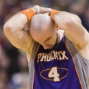 Phoenix Suns' Marcin Gortat holds his head after falling onto the court during the second half of an NBA basketball game agai