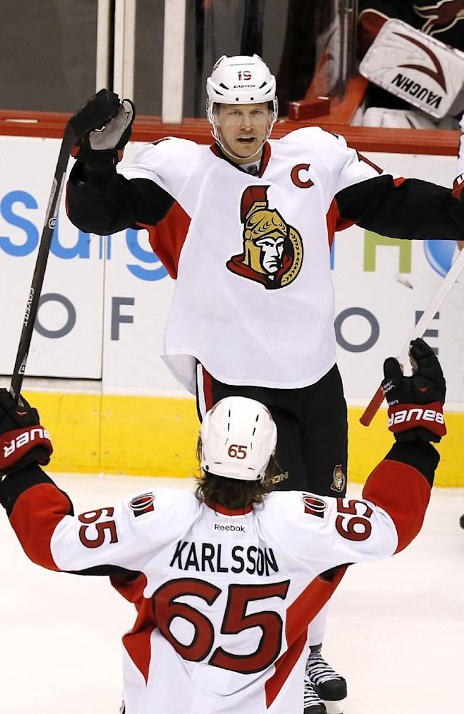 Ottawa Senators' Jason Spezza (19) celebrates his third goal of the game against the Phoenix Coyotes with teammate Erik Karlsson (65), of Sweden, during the third period in an NHL hockey game on Tuesday Oct. 15, 2013, in Glendale, Ariz.  The Senators defeated the Coyotes 4-3 in overtime