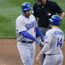 Los Angeles Dodgers' Adrian Gonzalez, left, is congratulated as he crosses home plate after hitting a two-run home run by teammate Enrique Hernandez against the Colorado Rockies in the third inning of Game 2 of a baseball doubleheader Tuesday, June 2, 2015, in Denver. (AP Photo/David Zalubowski)