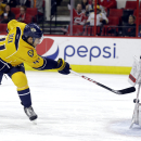 Carolina Hurricanes goalie Cam Ward (30) blocks Nashville Predators' Taylor Beck during the first period of an NHL hockey game in Raleigh, N.C., Tuesday, Dec. 2, 2014 The Associated Press