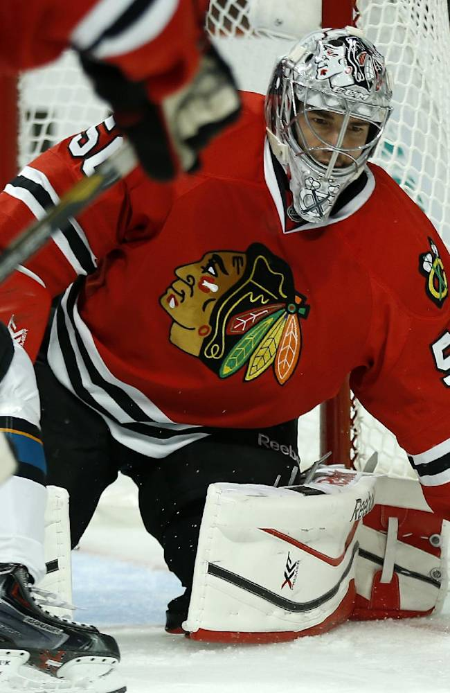 Chicago Blackhawks goalie Corey Crawford (50) deflects a San Jose Sharks puck during the first period of an NHL hockey game on Sunday, Nov. 17, 2013, in Chicago