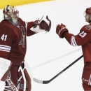 Phoenix Coyotes' Mike Smith (41) celebrates a shutout win with teammate Oliver Ekman-Larsson (23), of Sweden, at the end of the third period in an NHL hockey game against the Vancouver Canucks on Tuesday, March 4, 2014, in Glendale, Ariz. The Coyotes def
