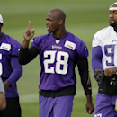 Minnesota Vikings running back Adrian Peterson, center, waves to fans as he walks to the field with wide receiver Greg Jennings, left, and defensive end Everson Griffen, right, during NFL football training camp, Sunday, July 27, 2014, in Mankato, Minn The