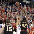 Gonzaga's Kevin Pangos (4) puts up a 3-pointer and scores over Santa Clara's Raymond Cowels III (42) and Marc Tasolini (15), in the first half of an NCAA college basketball game, Wednesday, Feb. 20, 2013, in Spokane, Wash. (AP Photo/Jed Conklin)