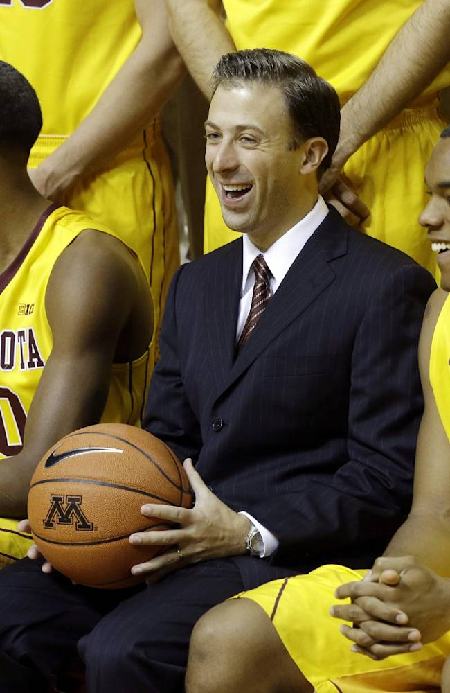 New Minnesota head basketball coach Richard Pitino, center, enjoys a laugh along with, from left, Maverick Ahanmisi, Austin Hollins and right, Andre Hollins (no relation) during set up for the formal team portrait during media day, Monday, Oct. 28, 2013, in Minneapolis