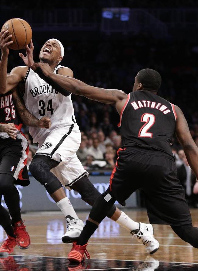 Brooklyn Nets forward Paul Pierce (34) reacts as he is sandwiched between Portland Trail Blazers point guard Mo Williams (25) and Trail Blazers guard Wesley Matthews (2) while driving toward the basket in the first half of their their NBA basketball game at the Barclays Center, Monday, Nov. 18, 2013, in Brooklyn